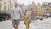 suécia : Couple walking holding hands in city of Stockholm, Sweden, Europe. Happy multiracial young couple walking outside on Stortorget big square in Gamla Stan, the old town. Scandinavian man, Asian woman.