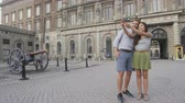 suécia : Tourists couple taking selfie photo with smartphone of Stockholm Royal Palace, Sweden, Europe. Happy tourist people visiting landmarks and attractions in Gamla Stan, the old town of Stockholm Vídeos