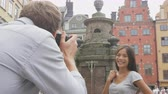suécia : Boyfriend taking picture of girlfriend using SLR camera. Couple in love dating having fun taking photos on travel. Tourists visiting Stockholm, Sweden. Multiracial Asian woman, Caucasian man. Vídeos