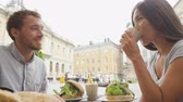 sanduíche : Couple eating food at Cafe in Stockholm, Sweden, Europe. Happy multiracial young couple outside on Stortorget big square in Gamla Stan, the old town of Stockholm. Scandinavian man, Asian woman.