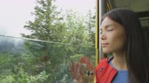 turistler : Woman enjoying looking at nature through tourist train window. Girl is on sightseeing tour. Attractive visitor is sitting in vehicle. She is enjoying vacation in Switzerland