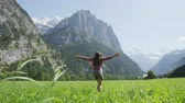 pole : Carefree young woman turning around on grassy field. Happy female with arms outstretched is enjoying in nature. Idyllic view of rocky mountains on sunny day. Swiss Alps, Switzerland.