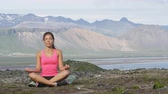 modelka : Meditating yoga woman in meditation in nature. Female model relaxing in serene harmony in lotus position pose. Healthy wellness lifestyle image with multicultural young woman. Image from Iceland.