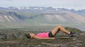 atleta : Fitness woman exercising single leg glute bridge exercise training butt and legs outside in beautiful nature landscape on Iceland. Fit female sports model working out.