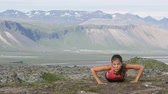 empurrão : Push-ups fitness woman doing pushups or plank outside in amazing nature landscape on Iceland. Fit female sport model girl training crossfit outdoors. Mixed race Asian Caucasian athlete in her 20s. Stock Footage