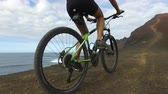 женщина : Woman cycling riding bicycle on mountain by sea on mountain bike. Sporty woman cyclist biking in nature. Active fitness girl living healthy lifestyle. ACTION CAMERA, Lanzarote, Canary Islands, Spain.