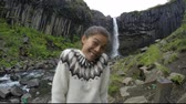 svartifoss : Woman enjoying against majestic Svartifoss waterfall. Female is visiting famous tourist attraction of Iceland. She is making faces at spectacular natural landmark on vacation. Skaftafell ACTION CAMERA Stock Footage