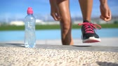 sedento : Sports woman runner getting ready for run tying laces of running shoes next to water bottle on athletic track and field background. Female athlete preparing for fitness cardio workout. Feet closeup.