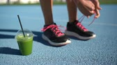 Female athlete runner getting ready for run race with green smoothie breakfast plastic cup tying running shoes on blue outdoor athletic track. Feet closeup.