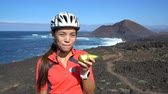 sağlıklı : Happy mountain biking woman eating healthy pear doing thumbs up on bike break in nature landscape. Asian athlete having a fruit snack on sports trip in beautiful outdoors living an active lifestyle.