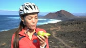 sağlıklı : Female mountain biker eating healthy pear on bike break in nature landscape. Happy Asian woman having a snack biting fruit on trail biking trip in beautiful outdoors living an active lifestyle.