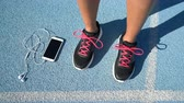 muzyka : Closeup of running shoes next to smartphone on blue athletic track. Woman runner ready to run holding her phone and earphones for music motivation during cardio workout outdoors.