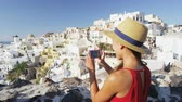 yolculuk : Happy woman tourist photographing beautiful village of Oia using smart phone.  Girl enjoying summer vacation travel visting viewpoint landmark destination  on Santorini, Greek Islands, Greece, Europe.