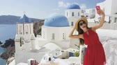 seyahat : Woman taking phone selfie On travel in Oia, Santorini using smartphone by blue domed church. Female tourist sightseeing enjoying summer vacation visiting landmark destination in Greece, Europe