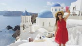ver��o : Woman taking phone selfie On travel in Oia, Santorini using smartphone by blue domed church. Female tourist sightseeing enjoying summer vacation visiting landmark destination in Greece, Europe