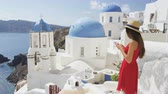 yolculuk : Tourist woman using mobile smart phone on travel. Young female using smartphone app by whitewashed blue domes of church. Girl on summer vacation in  Oia, Santorini, Greek Islands, Greece, Europe.