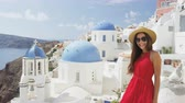 bonito : Woman with presenting showing welcome gesture in Oia Santorini, Greece, Europe. Young tourist is visiting famous landmark tourist destination wearing sunhat, sunglasses and red dress. SLOW MOTION.