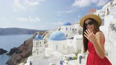 czerwony : Woman welcome you to walk with her on Santorini. Female tourist is enjoying summer vacation travel showing welcoming gesture smiling happy. Traditional typical Oia village, Santorini, Greece, Europe.