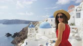 típico : Beautiful young woman enjoying her vacation On Santorini. Happy tourist is wearing sunhat, sunglasses and red dress standing by traditional whitewashed buildings, Oia, Santorini, Greece, Europe.