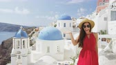 cúpula : Excited young woman waving hello at village Oia, Santorini, Greece, Europe. Young tourist is visiting famous landmark tourist destinations wearing sunhat, sunglasses and red dress. SLOW MOTION.