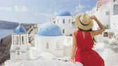 feliz : Tourist woman enjoying view of beautiful whitewashed village of Oia with blue domes on church. Young stylish female model wearing sunhat and red dress enjoying summer travel vacation in Europe.