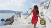 czerwony : Santorini Oia Blue Dome Church. Tourist woman on travel sightseing famous blue domed church landmark destination. Beautiful girl in red dress on visiting the Greek island Wideo