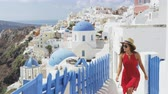 caminhada : Travel tourist woman in Oia, Santorini, Greece. Happy young woman walking on stairs by famous blue dome church landmark destination. Beautiful girl in red dress on visiting the Greek island.