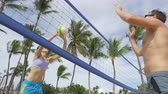 voleibol : People playing beach volleyball having fun in sporty active lifestyle. Man hitting volley ball in game in summer. Woman and man fitness model living healthy lifestyle doing sport on beach.