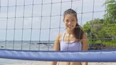 voleibol : Happy beach volleyball woman player. Portrait of smiling woman behind beach volley ball net looking at camera. Mixed race Asian Caucasian woman athlete