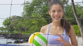 voleibol : Beach volleyball woman player. Fun Portrait of laughing woman throwing beach volley ball at net and looking at camera. Mixed race Asian Caucasian woman athlete