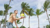 生活方式 : Beach volleyball serve - man serving in beach volley ball game on beautiful summer day. Young people having fun in the sun living healthy active sports lifestyle outdoors. Underhand serve