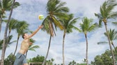 voleibol : Beach volleyball serve - man serving in beach volley ball game on beautiful summer day. Overhand spike serve. Young people having fun in the sun living healthy active sports lifestyle outdoors. Stock Footage
