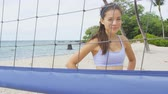 mixed race : Beach volleyball woman player. Portrait of smiling woman behind beach volley ball net looking at camera. Mixed race Asian Caucasian woman athlete