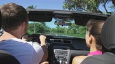 сиденья : Couple driving convertible car cabriolet. Young romantic couple on travel holidays vacation laughing smiling having fun. Man driver behind steering wheel. Hawaii, USA. Стоковые видеозаписи