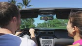 сиденья : Couple driving car on road trip travel vacation in convertible. Young romantic couple on travel holidays vacation laughing smiling having fun. Man driver behind steering wheel. RED EPIC, SLOW MOTION.