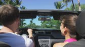 сиденья : Car couple driving on road trip travel vacation in convertible. Young romantic couple on travel holidays vacation laughing smiling having fun. Man driver behind steering wheel. RED EPIC, SLOW MOTION.