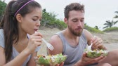 posiłek : Salad - healthy fitness woman and man couple talking and eating food lunch sitting on beach after workout. Mixed race Asian Caucasian female model and male models in sportswear.