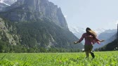 natureza : Happy woman having fun running in field nature excited of joy happiness. Joyful active lifestyle with free girl enjoying freedom, Lauterbrunnen valley, Swiss Alps, Switzerland