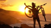 vítěz : Aspirations. Active lifestyle MTB cyclist mountain biking woman cheering happy raising arms lifting bike by sea during sunset celebrating successful achievement. Person with bicycle in amazing nature.