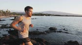 Fitness runner man running at sunset on beach trail. Healthy living sport model jogging working out exercising healthy lifestyle outdoor. Fit male model outside in SLOW MOTION