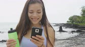 ázsiai : Fitness woman looking at phone app on beach. Running woman using smartphone application resting relaxing with water bottle after workout exercise on beach outside. Mixed race Asian Caucasian girl.