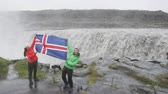 wodospad : Travel tourists fun by Dettifoss waterfall on Iceland showing Icelandic flag. People visiting famous tourist attractions and landmarks on Diamond Circle. Happy tourist couple enjoying vacation travel.