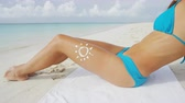 cal : Sunscreen solar cream uv protection concept - sun drawing in sunblock lotion on sexy woman thigh leg skin wearing blue bikini. Suntan on the Caribbean beach tropical vacation. Healthy skincare.