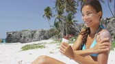 bloco : Sunscreen woman applying suntan lotion on bikini body. Beautiful smiling happy asian woman with suntan cream in bottle lying on beach during summer travel vacation. Multiracial female model