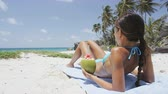 local : Sunbathing bikini woman relaxing lying down tanning under the tropical sun on Caribbean beach travel holiday holding a green coconut fruit to drink refreshing healthy fresh fruit water.
