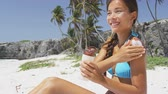 asie : Tropical beach bikini body woman applying sunscreen lotion on shoulder skin relaxing on Caribbean vacation getaway. Mixed race Asian girl putting sun cream - skincare solar protection.