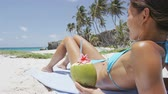 perda de peso : Sexy bikini slim body woman drinking healthy coconut water on beach vacation. Sunbathing weight loss model relaxing lying down in Barbados, Caribbean travel holiday.