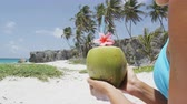 feriados : Fresh coconut water with straw on Caribbean beach in Barbados vacation. Unrecognizable woman in Barbados holding young green tropical fruit for healthy snack during summer holidays.