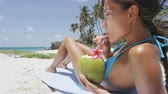 vacation : Happy beach fun bikini girl relaxing drinking healthy fresh coconut water on tropical suntan holiday on a Caribbean island. Woman enjoying the sun on summer vacation lying down on sand. Stock Footage