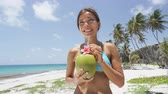 pessoas : Cute Asian girl on beach vacation drinking fresh coconut water from a green young coconut fruit cut from a palm tree. Healthy lifestyle woman eating local food on Caribbean travel holiday.